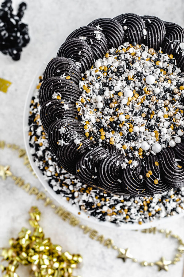 top view of black and gold cake with sprinkles in the centre