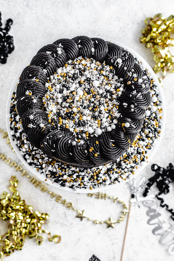full top view of black cake with sprinkles in centre