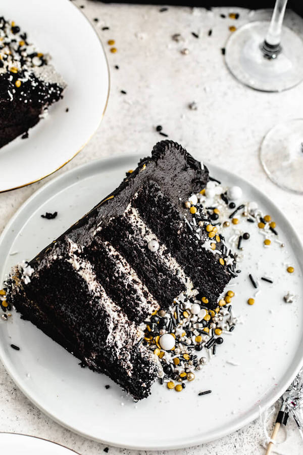 black dark chocolate champagne cake on a white plate