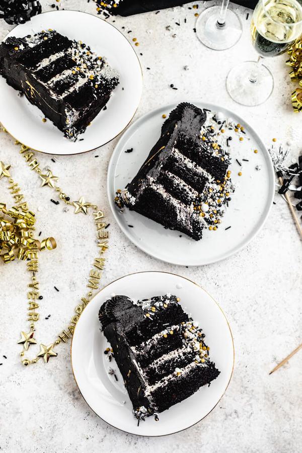 three slices of black cake on white plates