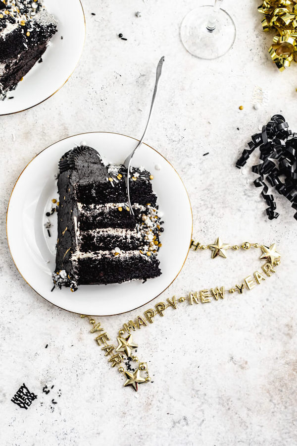 black cake on a white plate with fork inside and a happy new year's necklace underneath plate