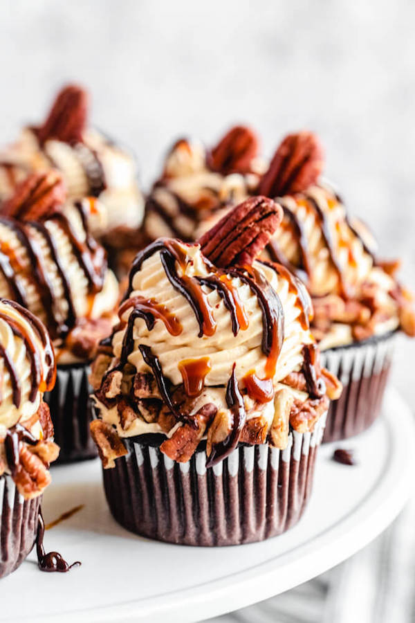 These Turtle Chocolate Cupcakes feature a moist and fudgy chocolate cupcake that's filled with pecan caramel sauce and topped with the most heavenly caramel cream cheese frosting! Multiple easy recipes come together to create cupcake perfection! | queensleeappetit.com #cupcakes #creamcheesefrosting #chocolatecupcakes