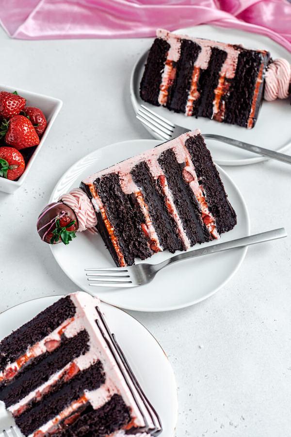 three slices of cake on white plates