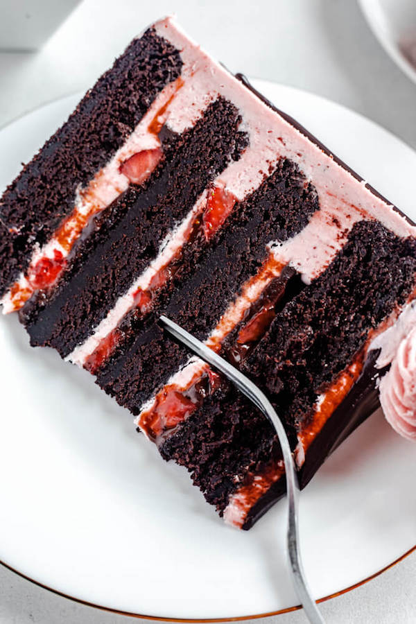 close up of a slice of cake on a white plate with fork inside