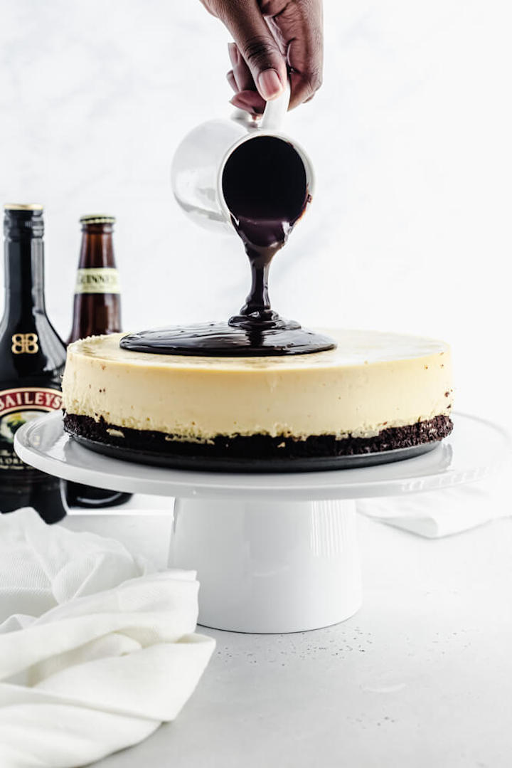 pouring ganache onto cheesecake