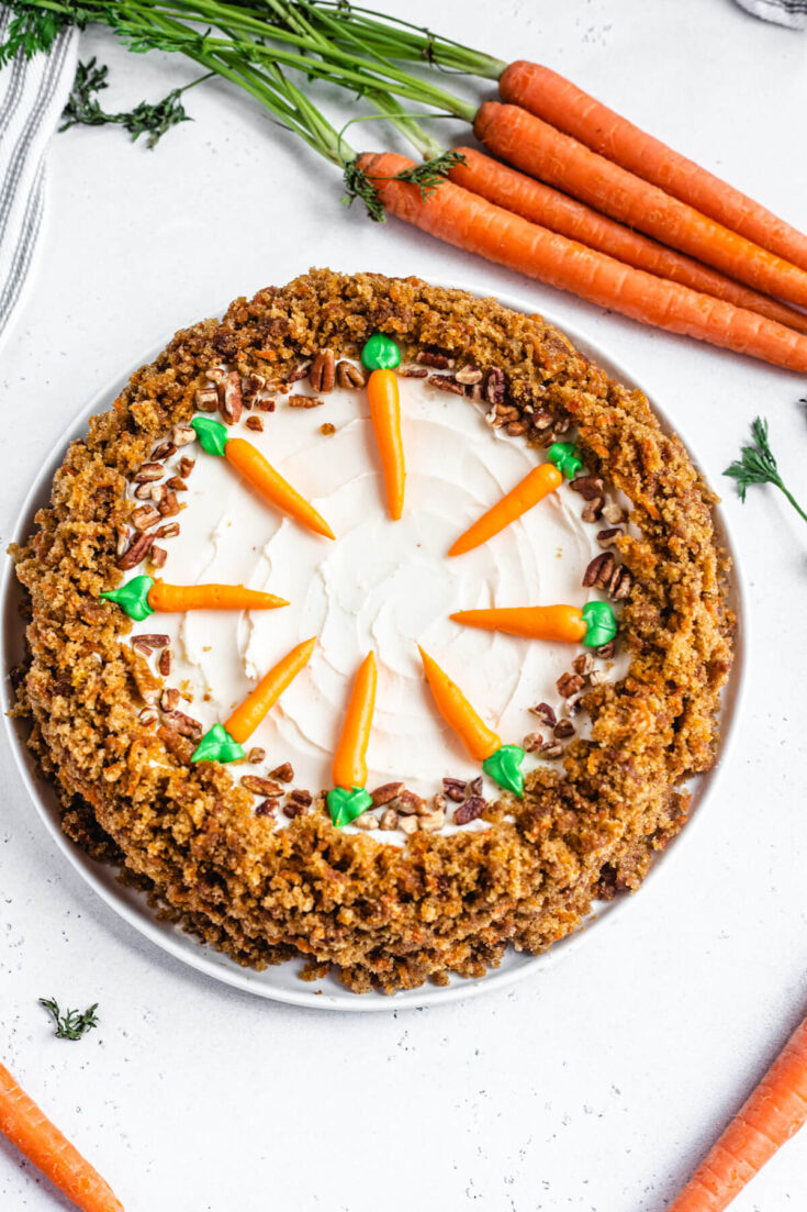 Carrot Cake and Cheesecake join forces to create the ultimate Carrot Cake Cheesecake! A delightful swirl of moist carrot cake and creamy cheesecake is coated in carrot cake crumbs and topped with cream cheese frosting and chopped pecans! | queensleeappetit.com #carrots #carrotcake #cheesecake #dessert