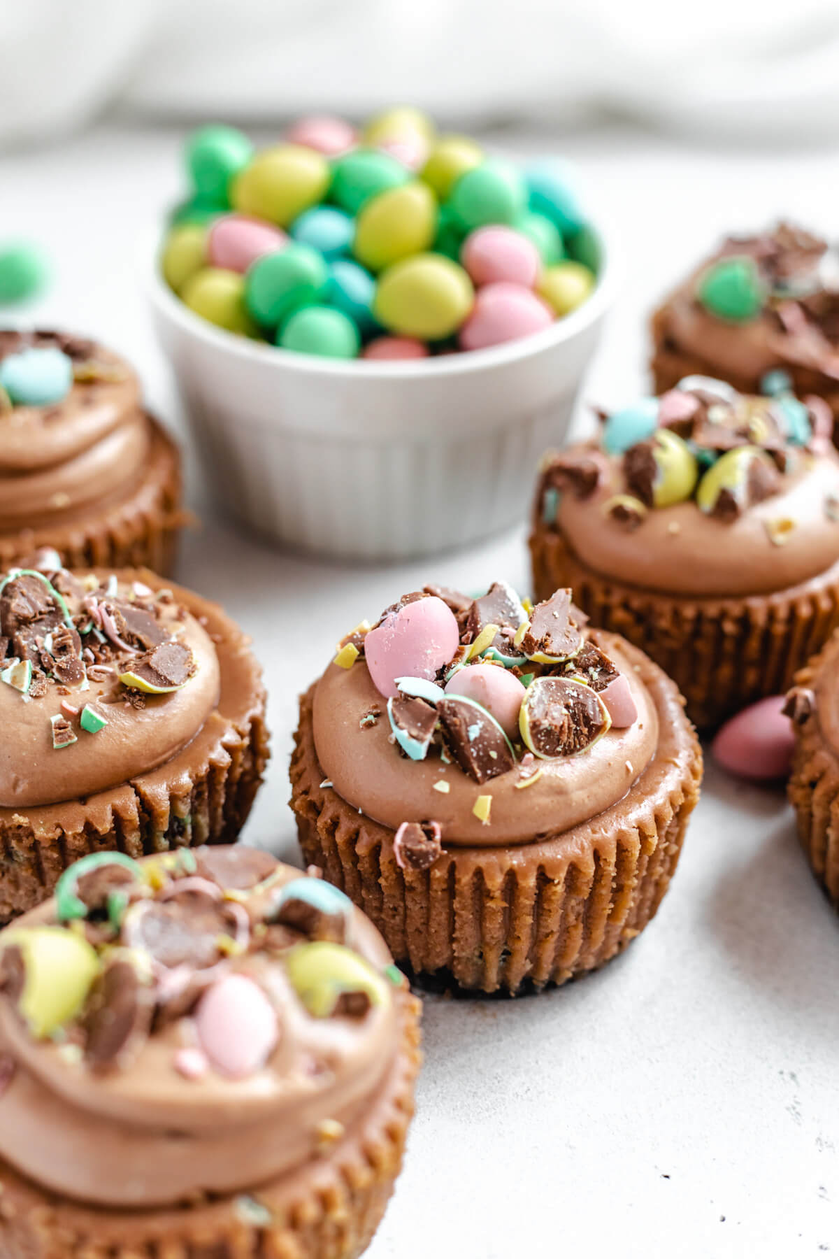 close up of multiple cheesecake cupcakes topped with mousse and chopped mini eggs