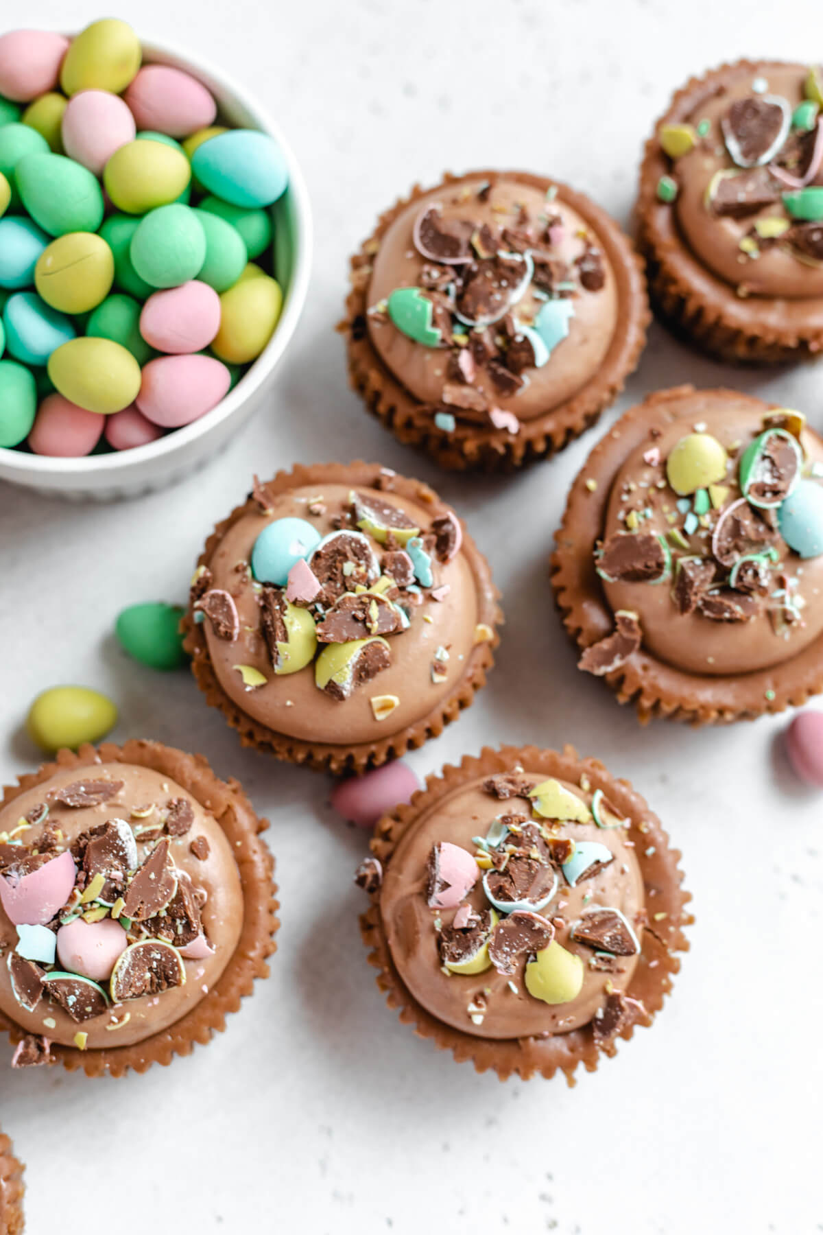 top view of small individual cheesecakes with mini chocolate eggs in a ramekin