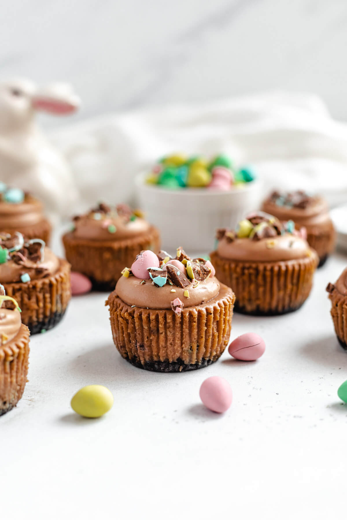 multiple mini cheesecakes topped with mousse and chopped chocolate eggs