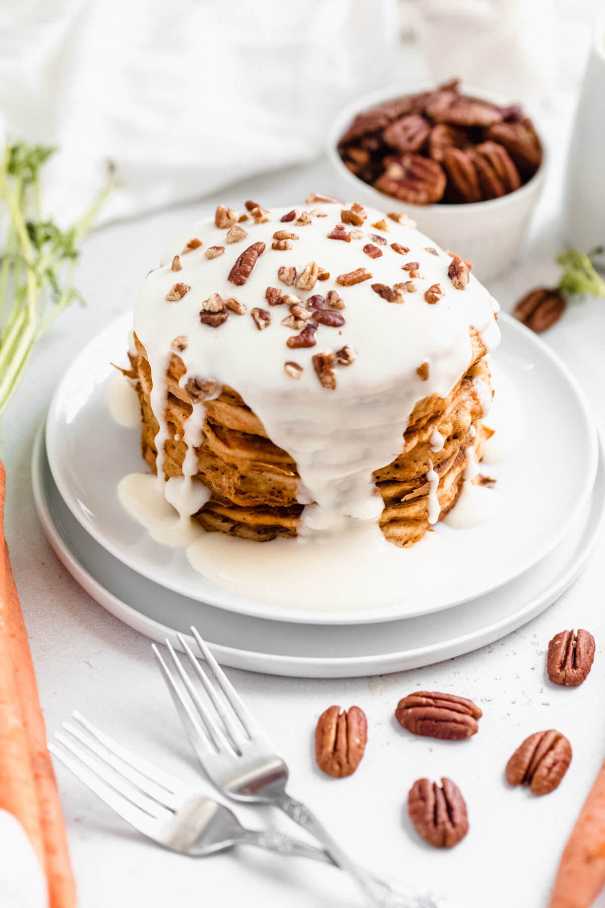 stack of pancakes topped with cream cheese glaze and chopped pecans