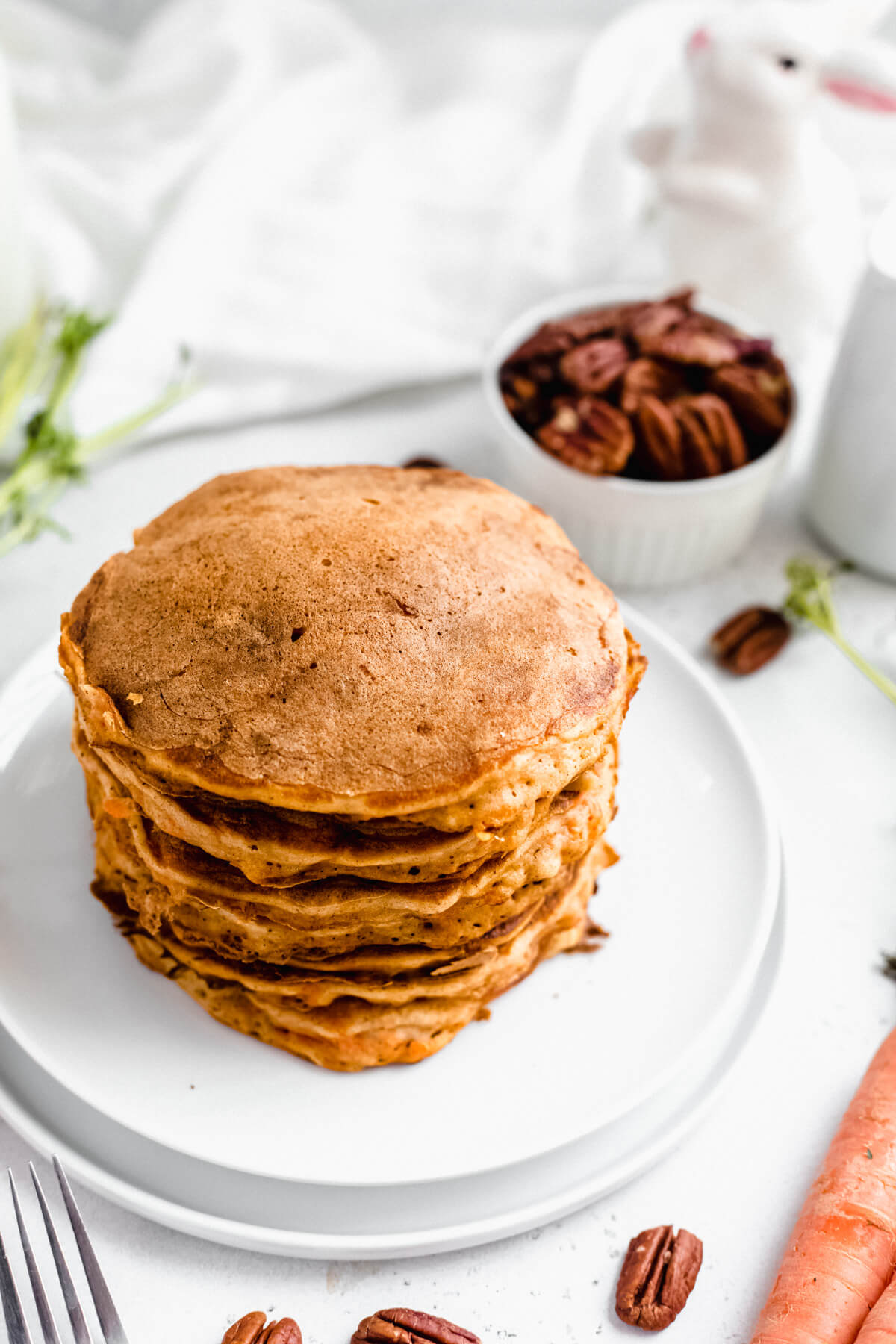stack of carrot pancakes on a white plate