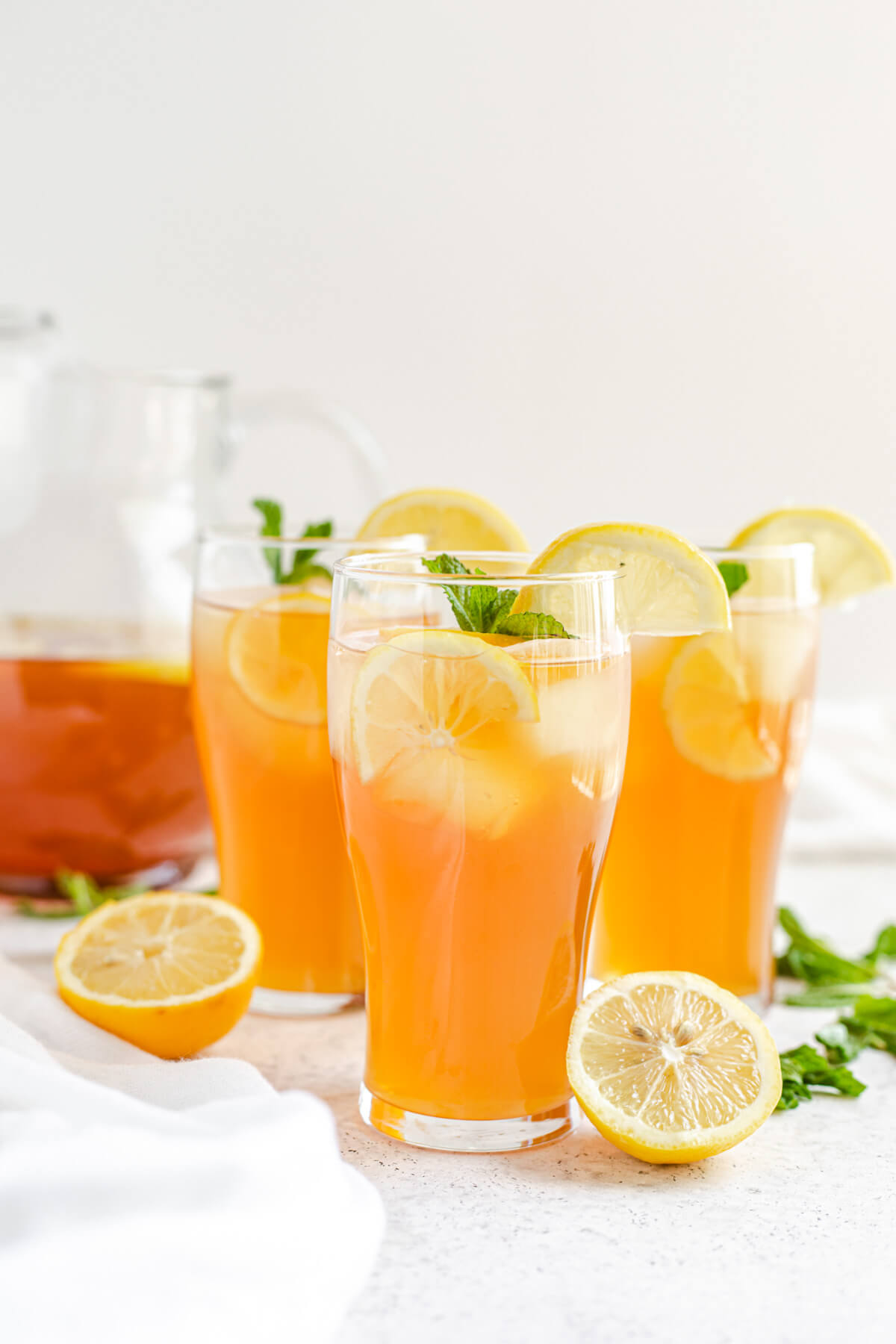 three glasses of iced tea with a glass pitcher in the background