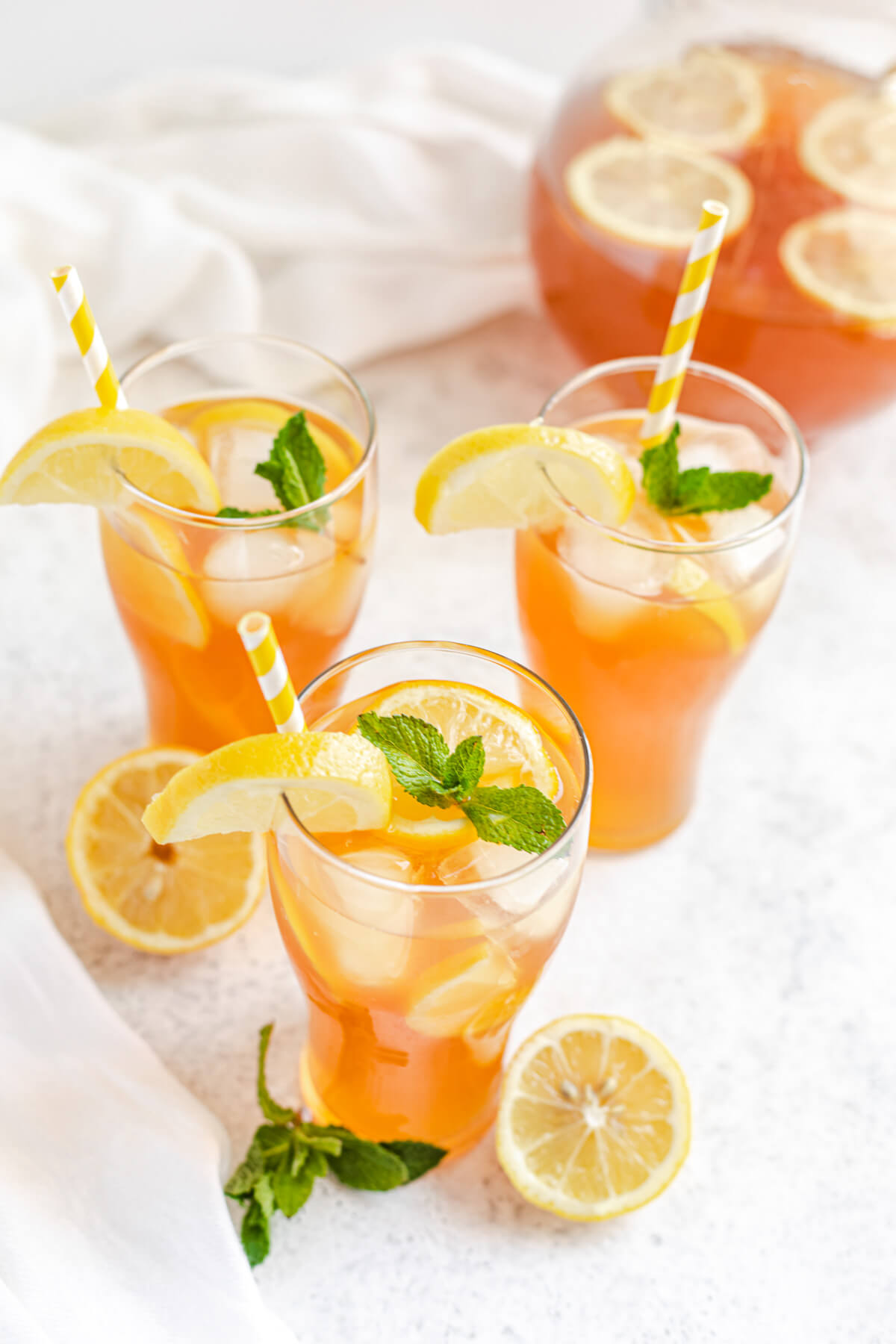 three glasses of lemon flavoured iced tea with striped yellow straws, fresh mint, ice and lemons inside and pitcher in the back