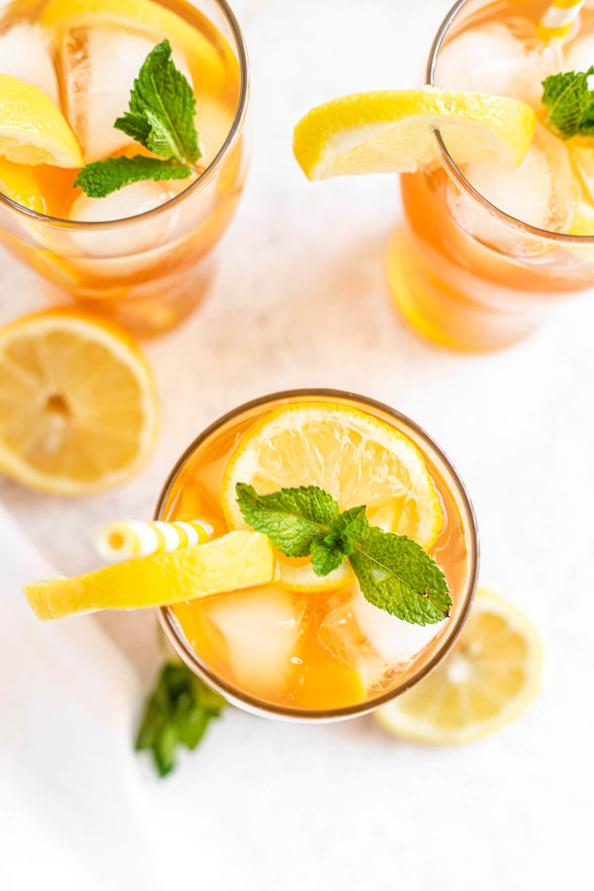 top down shot of sweet tea in a glass topped with ice cubes, fresh mint and sliced lemons