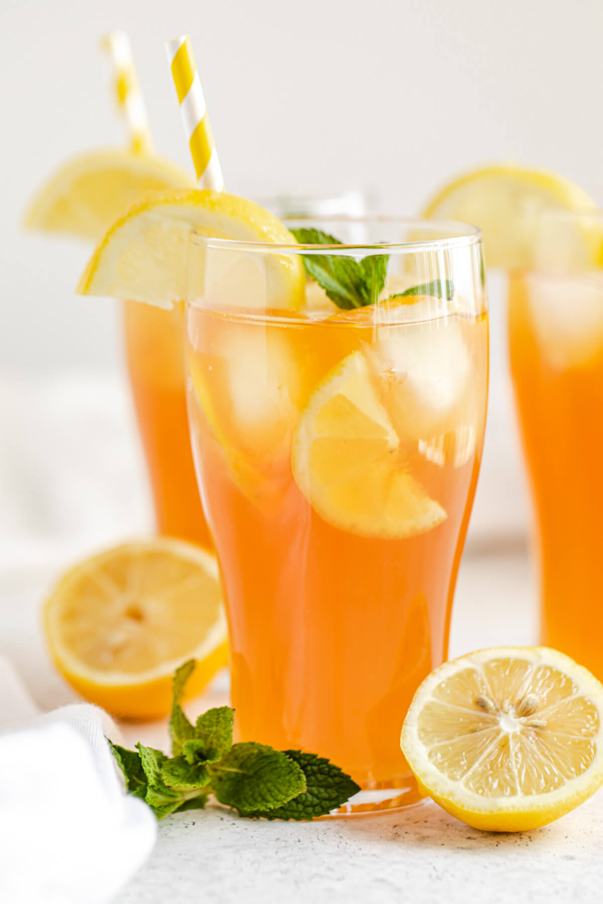 close up of three glasses of sweet tea with halved lemons and mint leaves inside and around the glasses