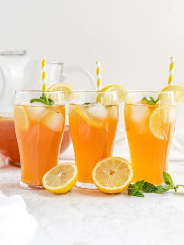 three glasses of iced tea with yellow striped straws and lemons and mint leaves in front of glasses