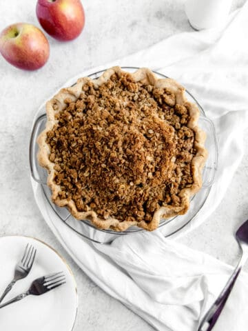 top of crumble pie with two apples, white scarf and white plates