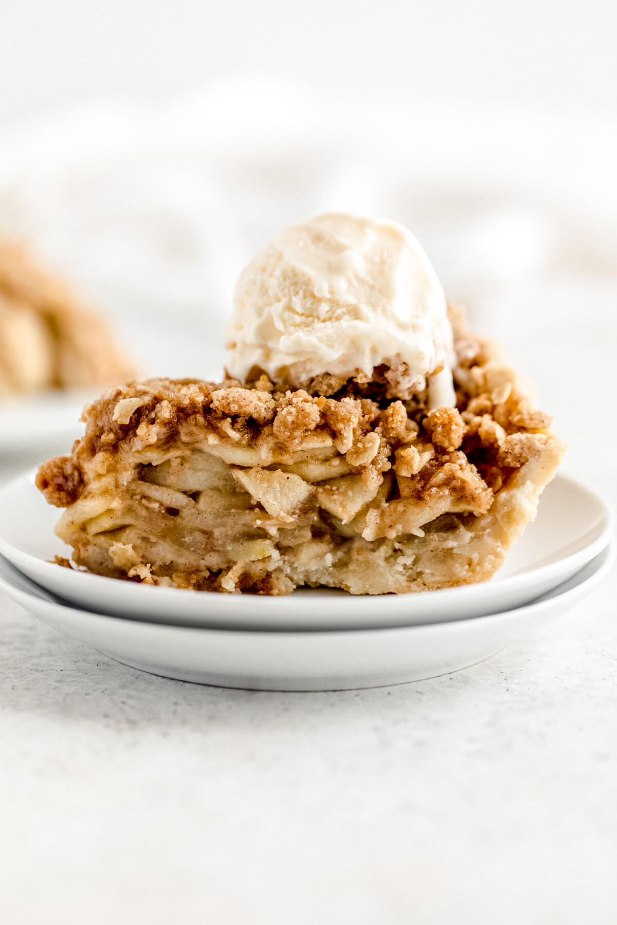 slice of apple pie topped with crumble and vanilla ice cream