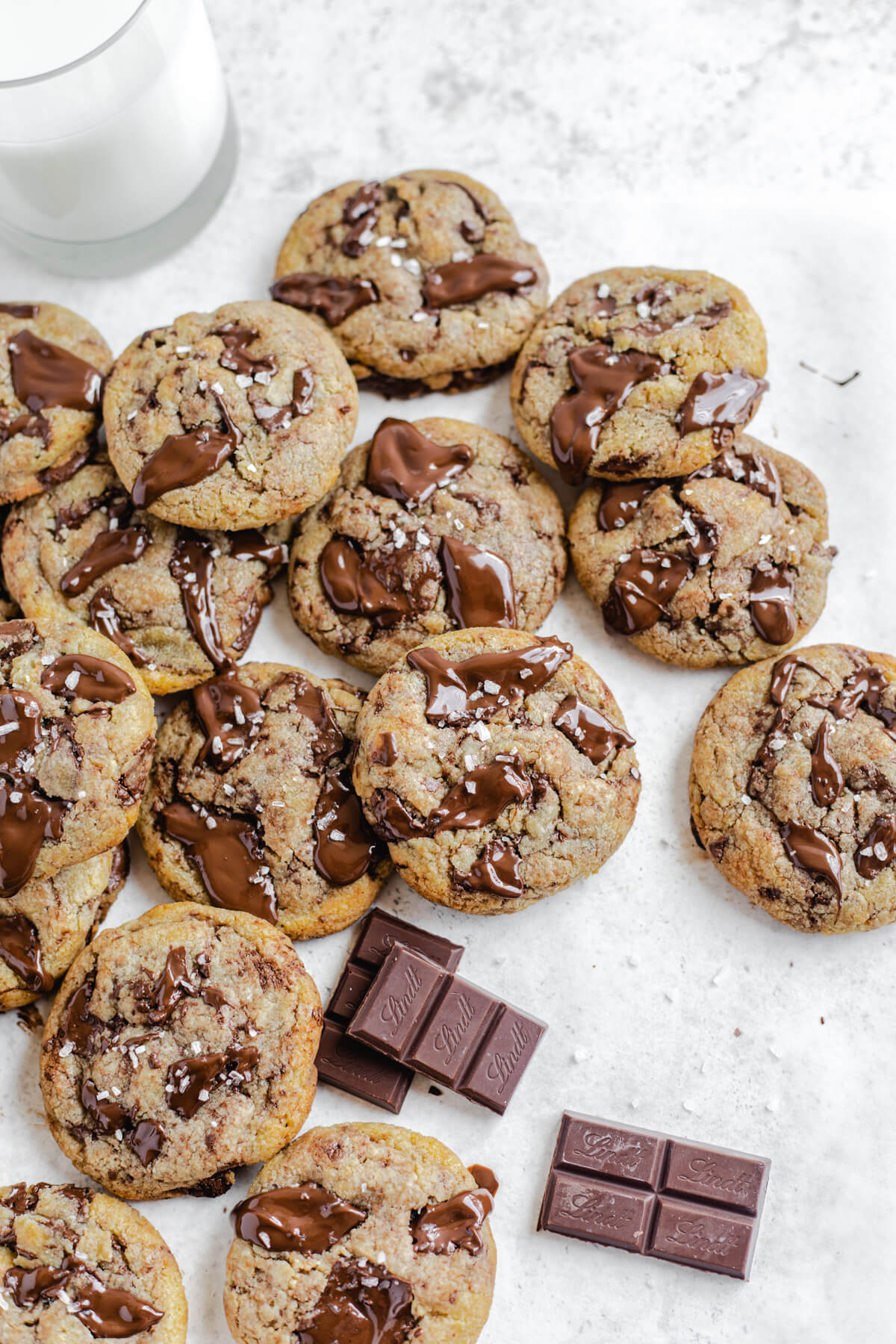 plenty of cookies piled close together with glass of milk in the back and dark chocolate pieces in the foreground