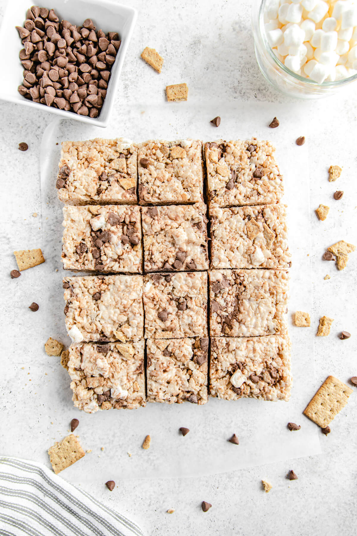 top shot of sliced s'mores flavoured Rice Krispie bars lined up together surrounded by chocolate chips, marshmallows and graham crackers