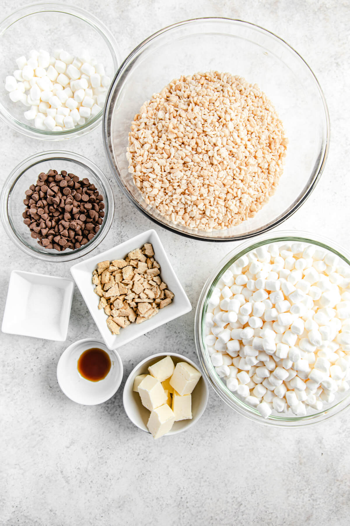 ingredient photo: bowls of Rice Krispies cereal, mini marshmallows, cubed butter, vanilla, salt, milk chocolate chips and crushed graham crackers