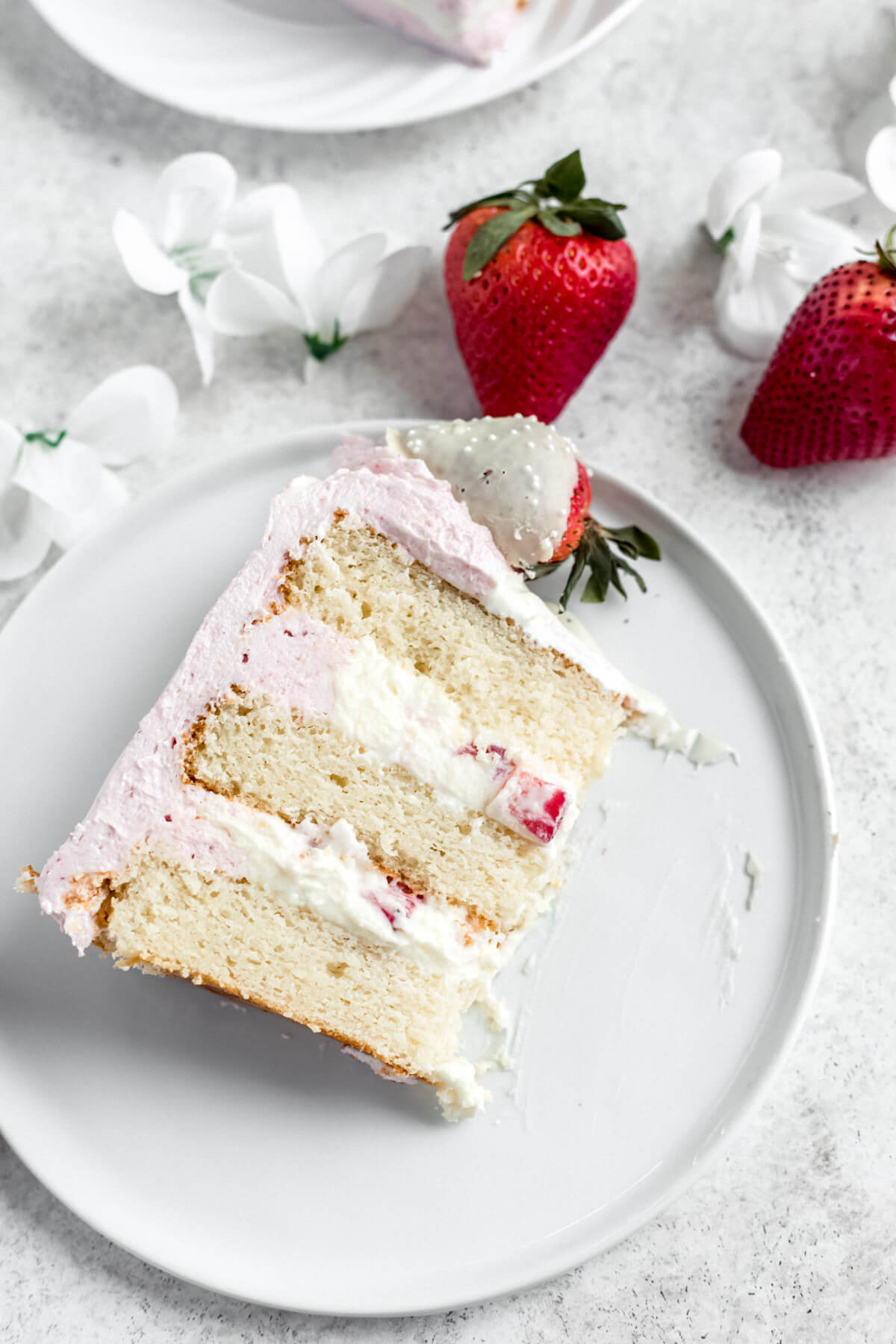 slice of white cake with mousse filling on a white plate with strawberries beside