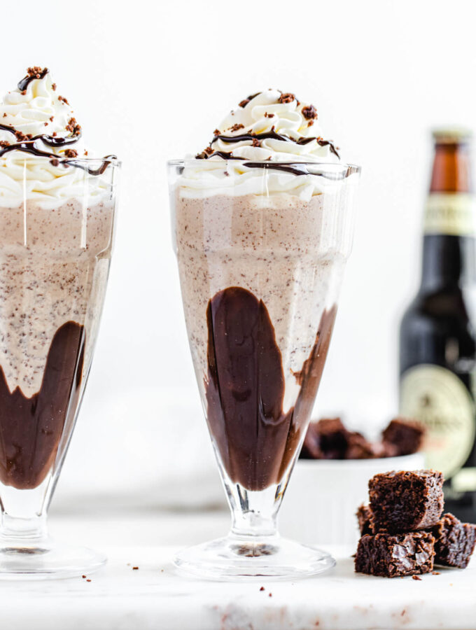 two milkshakes on a rectangle marble board with three brownie chunks beside them and a bottle of beer in the background