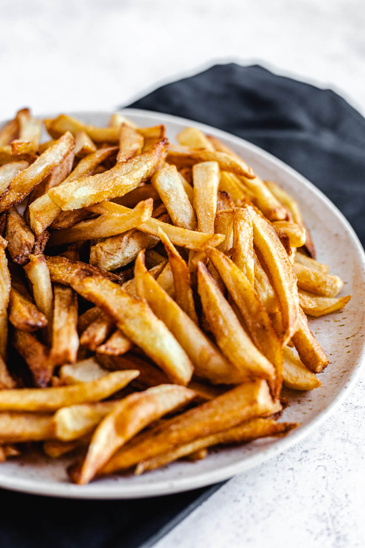close up of cooked French fries on a plate