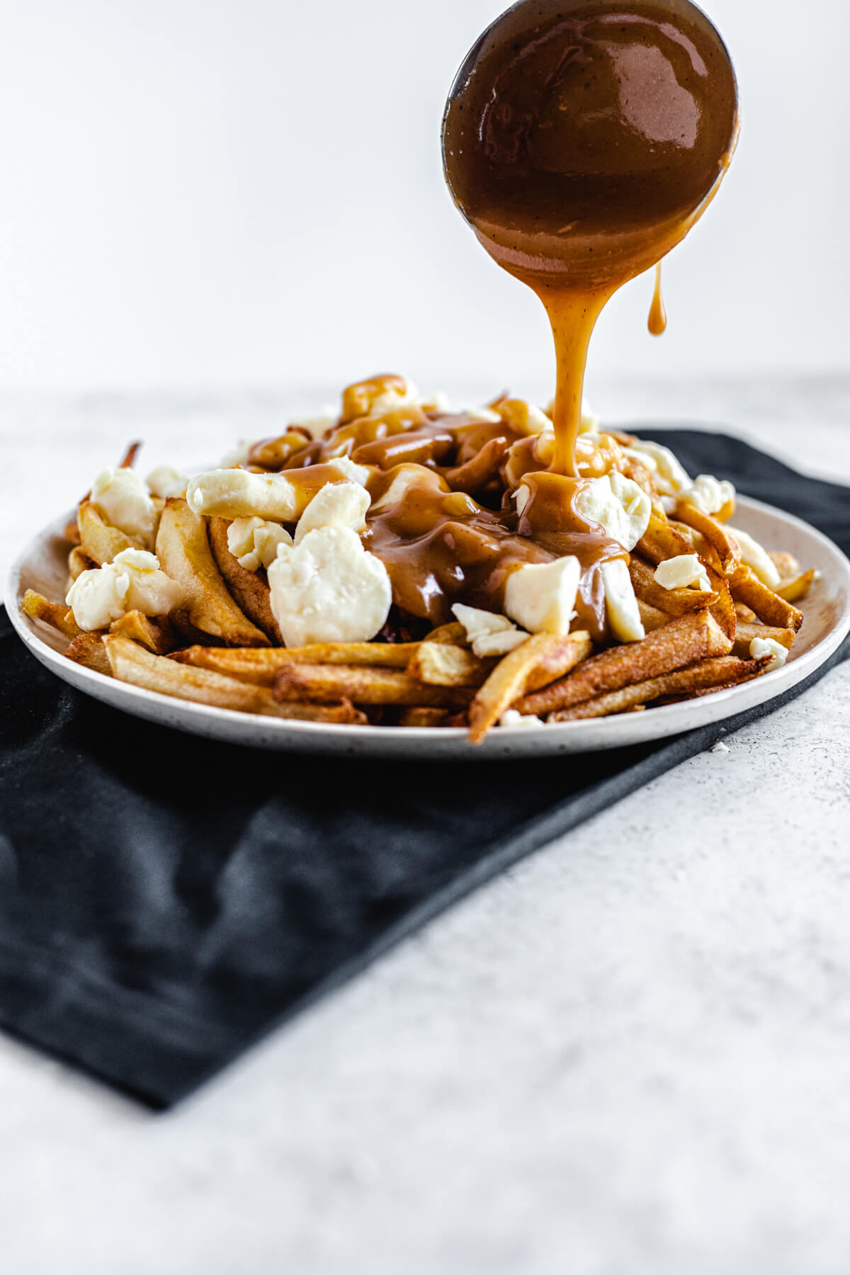 pouring gravy from a ladle onto a plate of fries and cheese curds