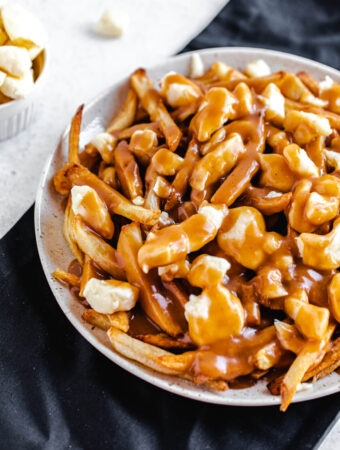 cheese, fries and gravy on a large plate that's on a black linen napkin