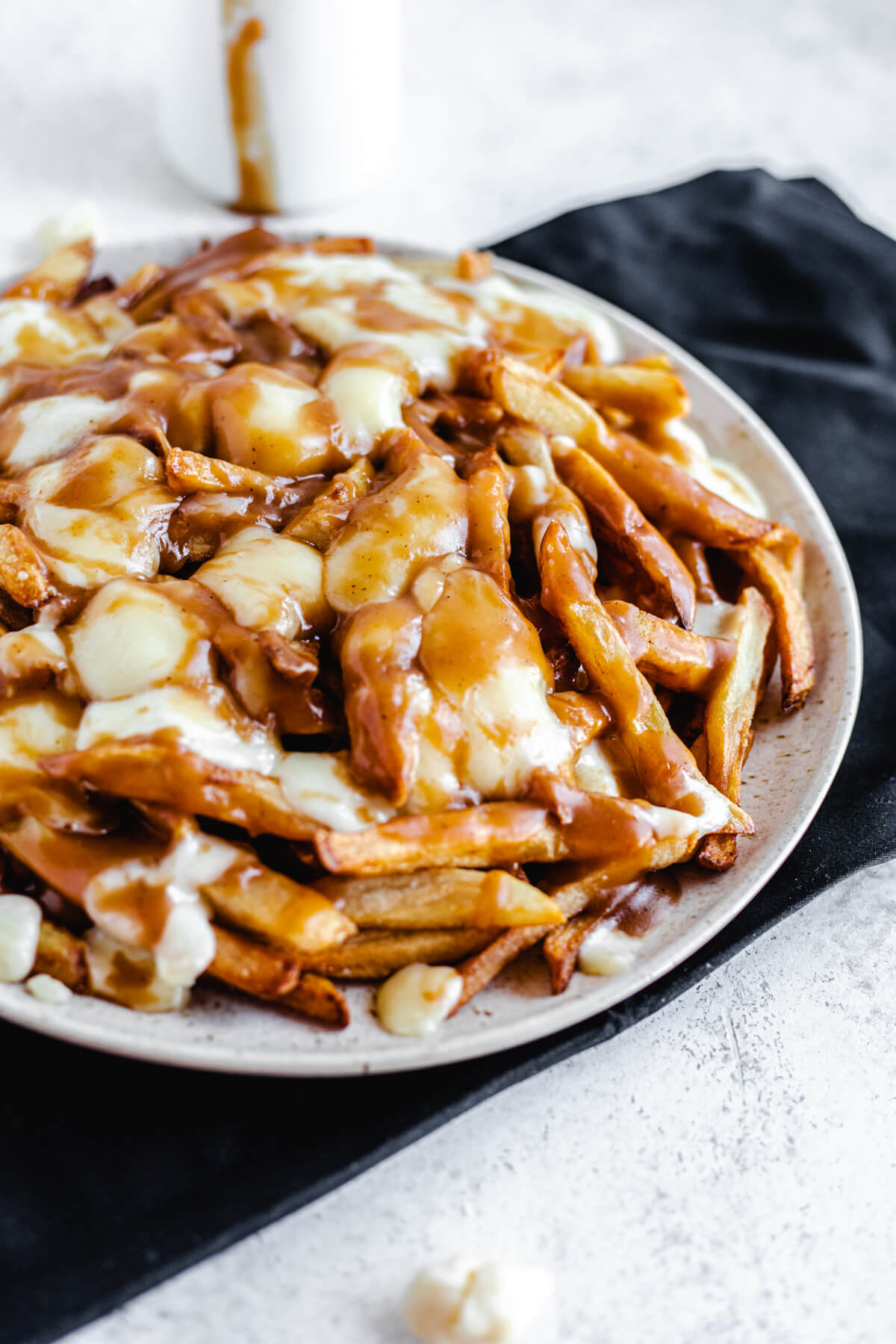 plate filled with homemade fries, cheese curds and brown gravy on a black rectangle cloth napkin