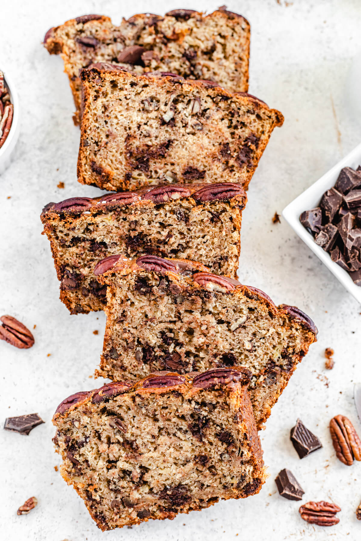 top shot of a row of banana bread slices with pecans and chocolate around them