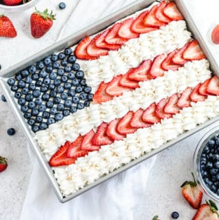 cheesecake decorated with whipped cream, sliced strawberries and blueberries to look like the American flag