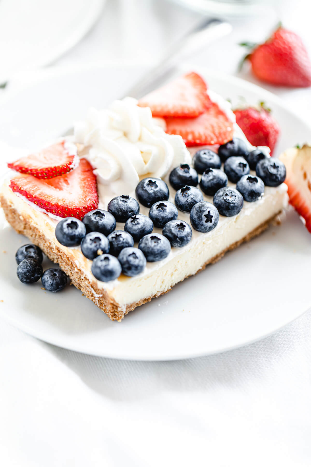 slice of cheesecake with blueberries, whipped cream and strawberries on top on a white plate