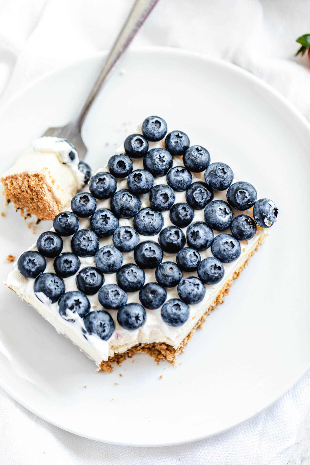 slice of cheesecake with blueberries on top on a white plate with forkful taken out