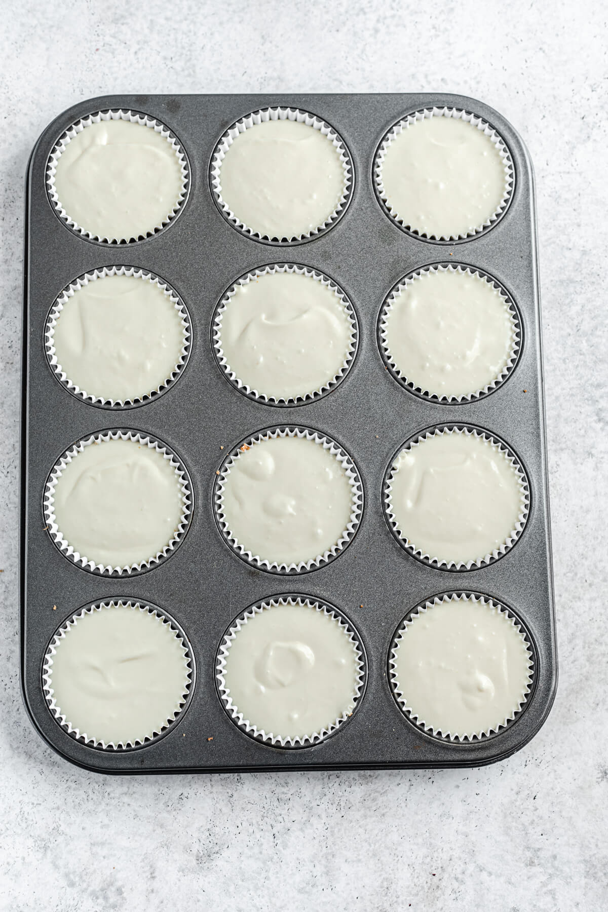 unbaked cheesecake batter in cupcake liners