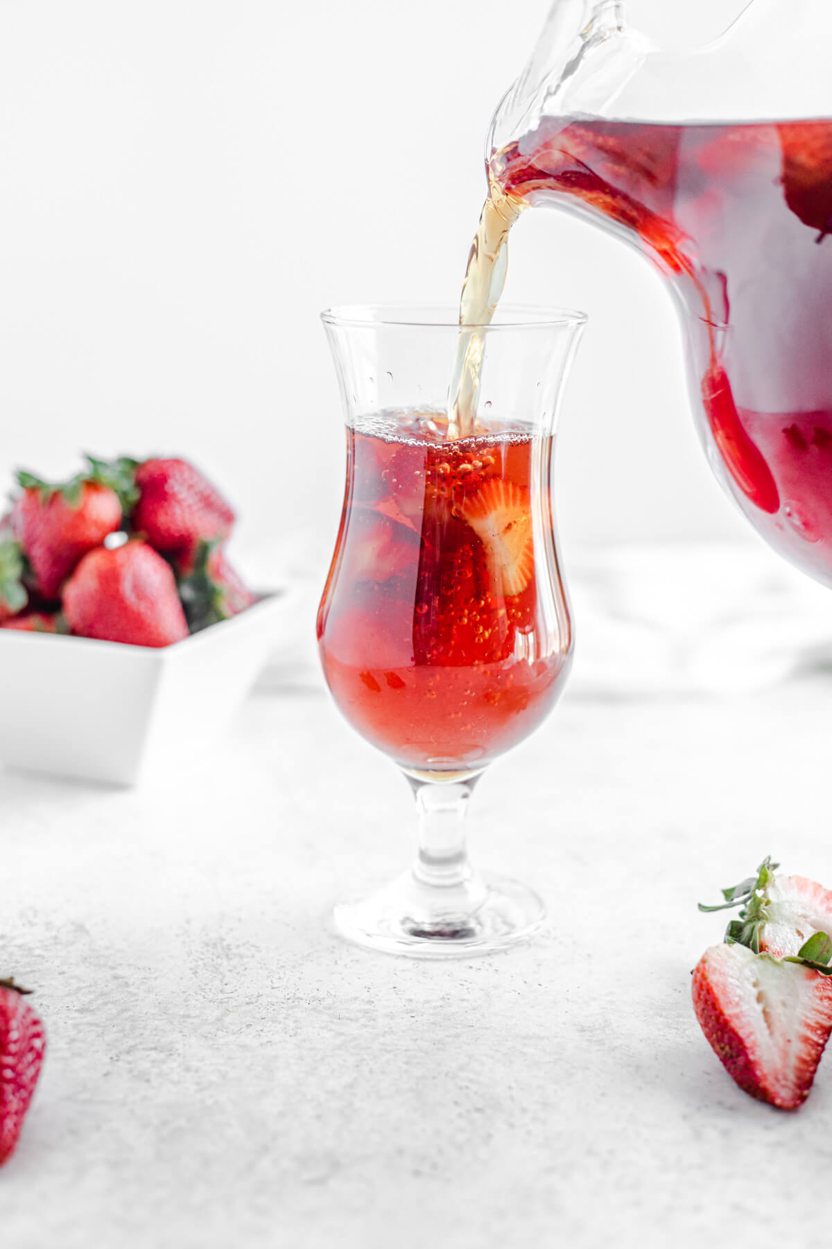 pouring strawberry flavoured iced tea into a glass filled with fresh sliced strawberries