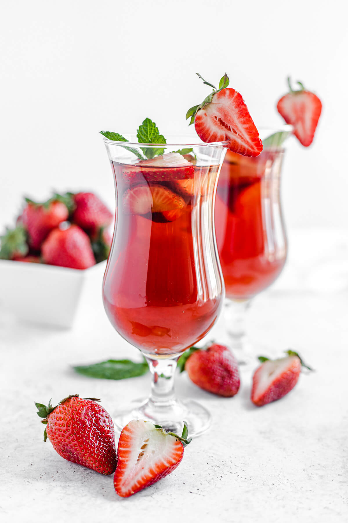 two glasses of iced tea with fresh mint and strawberries inside