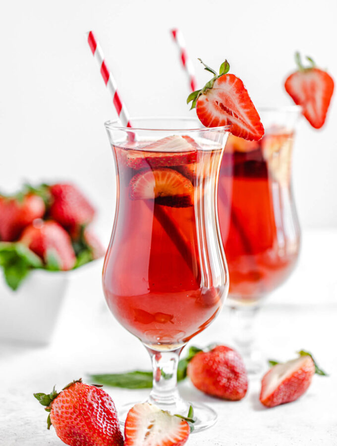 one glass of strawberry flavoured iced tea in the foreground and another glass in the background with fresh strawberries in front of the glasses and in a square white bowl in the background