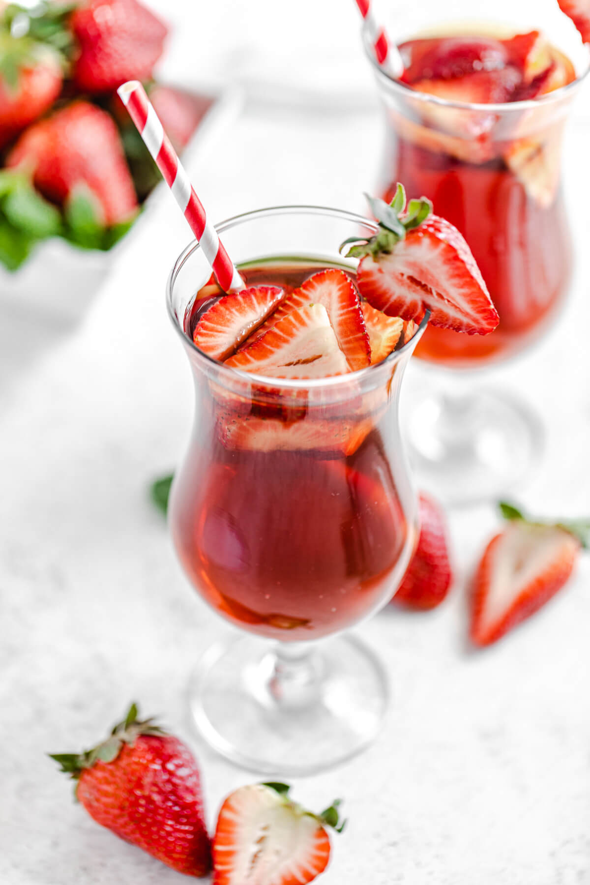 top angled view to show inside of glass with iced tea, fresh strawberries and a red striped paper straw inside