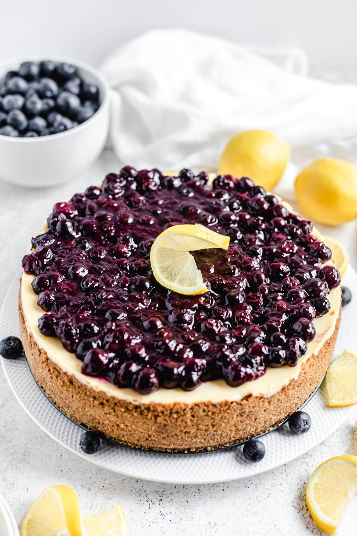 cheesecake on a large white plate with lemons and blueberries around and on top of it