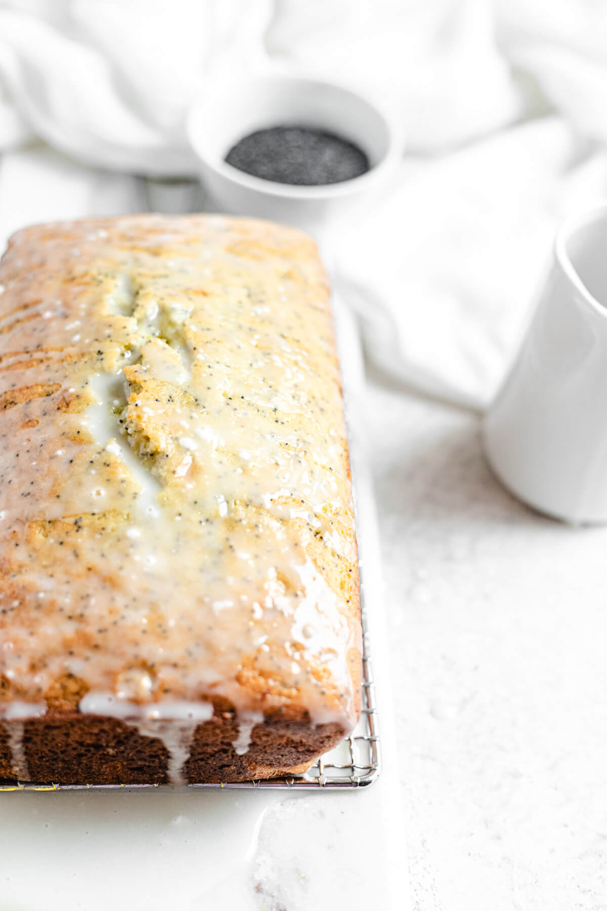 glazed loaf on a safety grater with a bowl of poppy seeds in the background