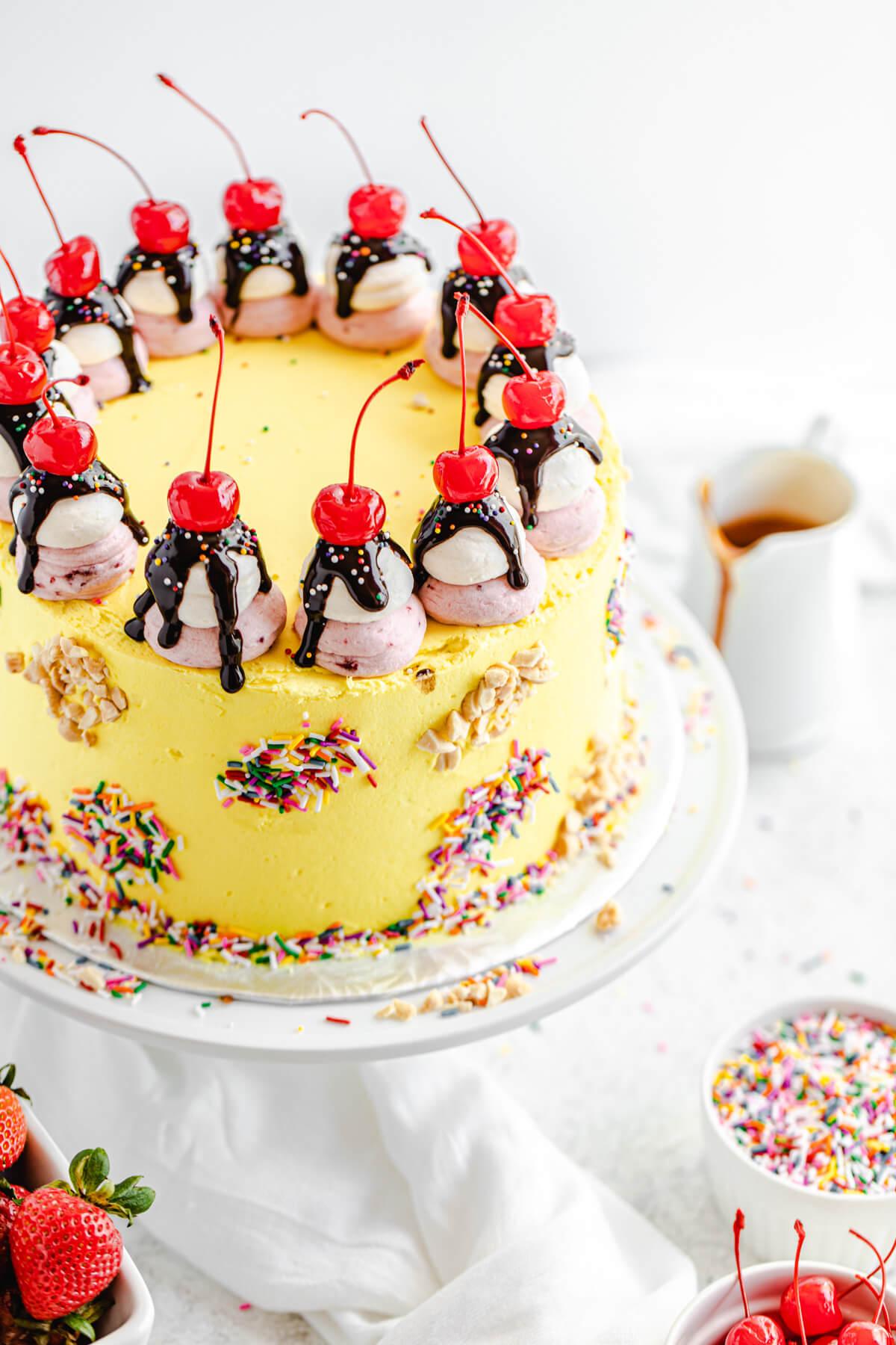 angled view of banana split cake on a cake stand