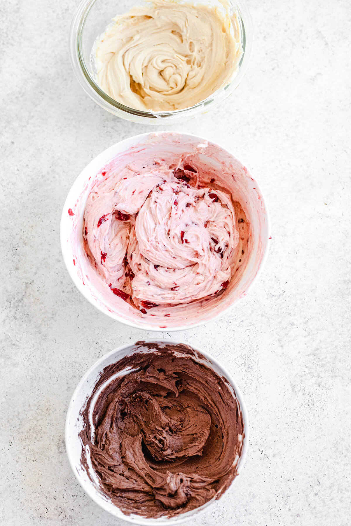 chocolate, strawberry and caramel frosting in three bowls