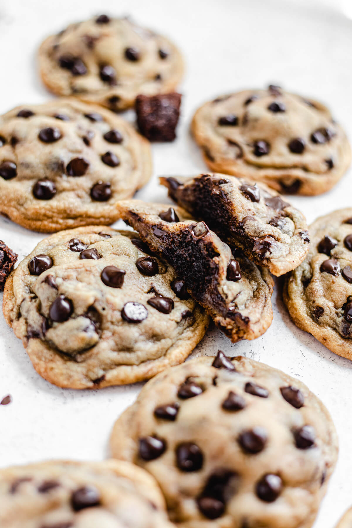 two halves of a cookie leaning on a chocolate chip cookie