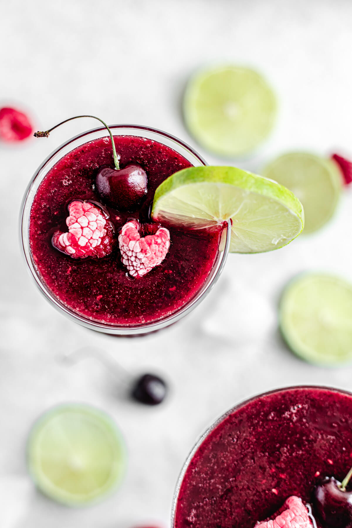 top view showing daiquiri inside of glass topped with two frozen raspberries, a cherry and a lime slice