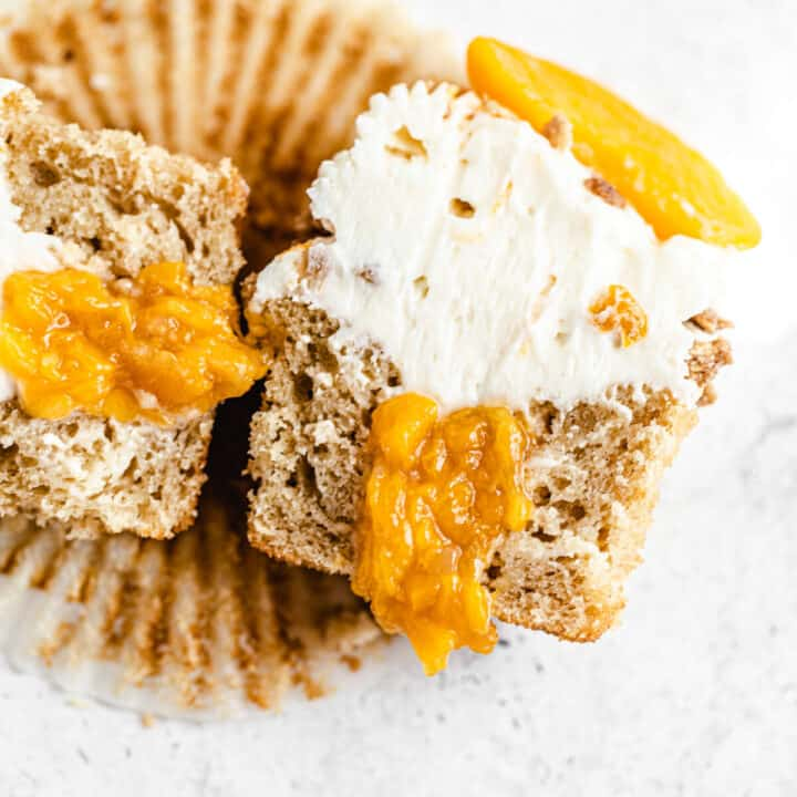 two halves of a cheesecake swirled cupcake with peach filling inside