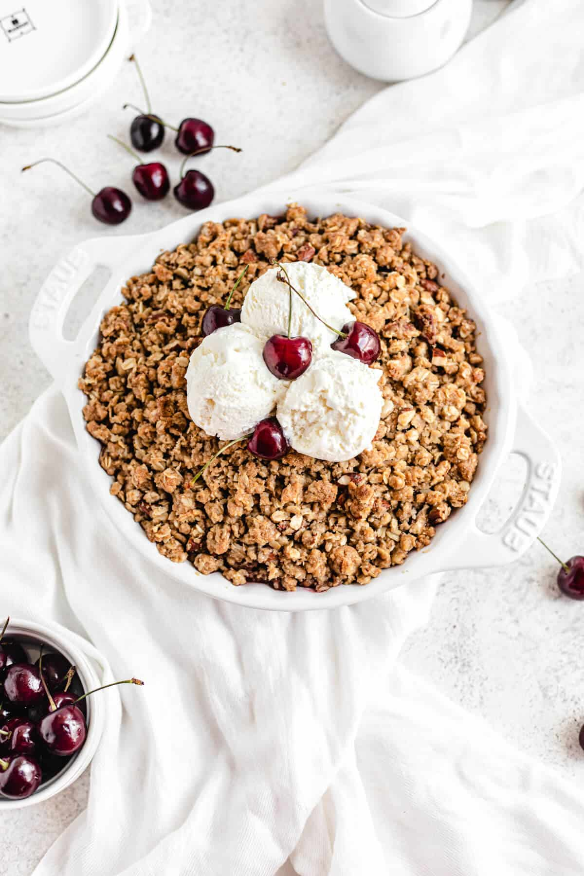 cherry crumble topped with three scoops of vanilla ice cream and fresh cherries