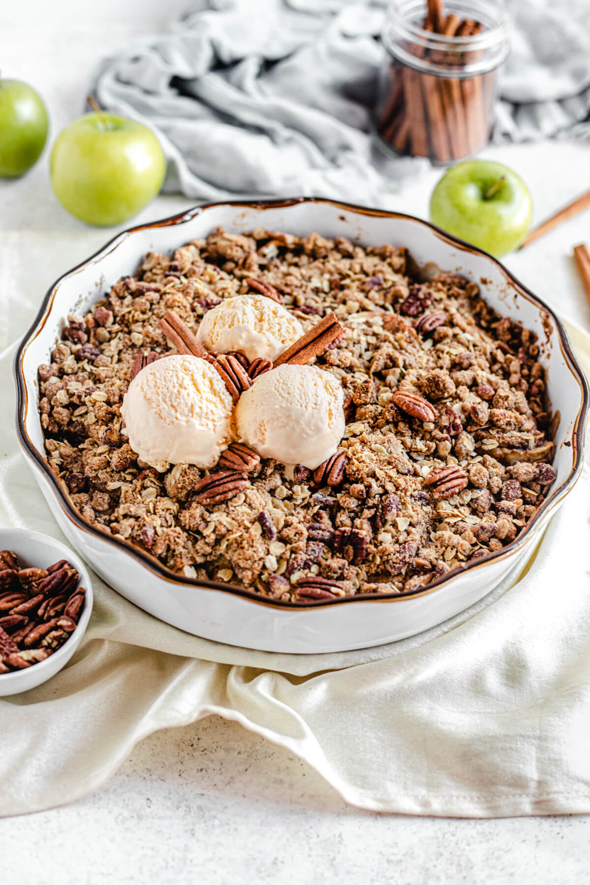 apple crisp in white pie dish topped with ice cream and cinnamon sticks