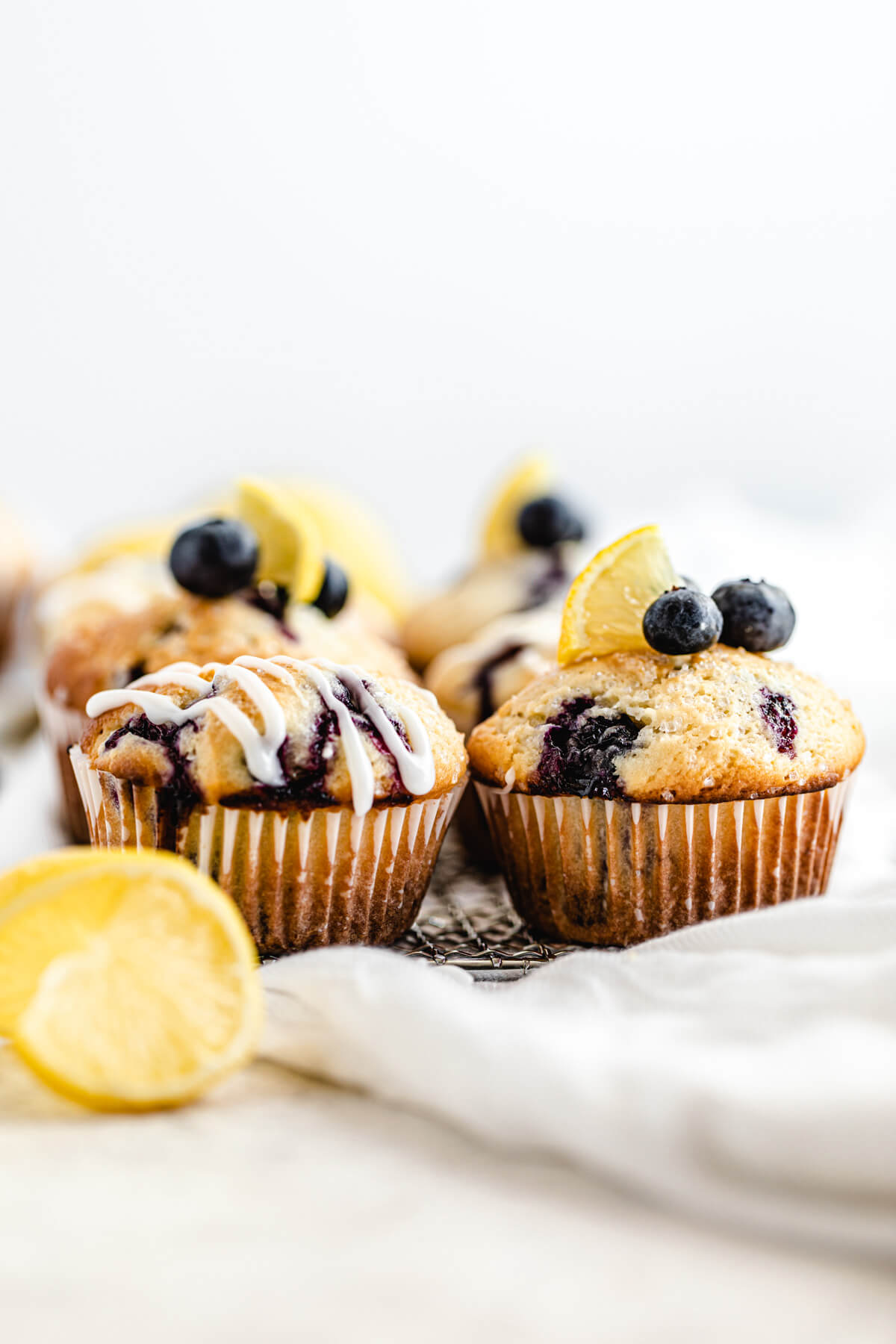 blueberry muffins lined up on a safety grater with lemon twist in front of them